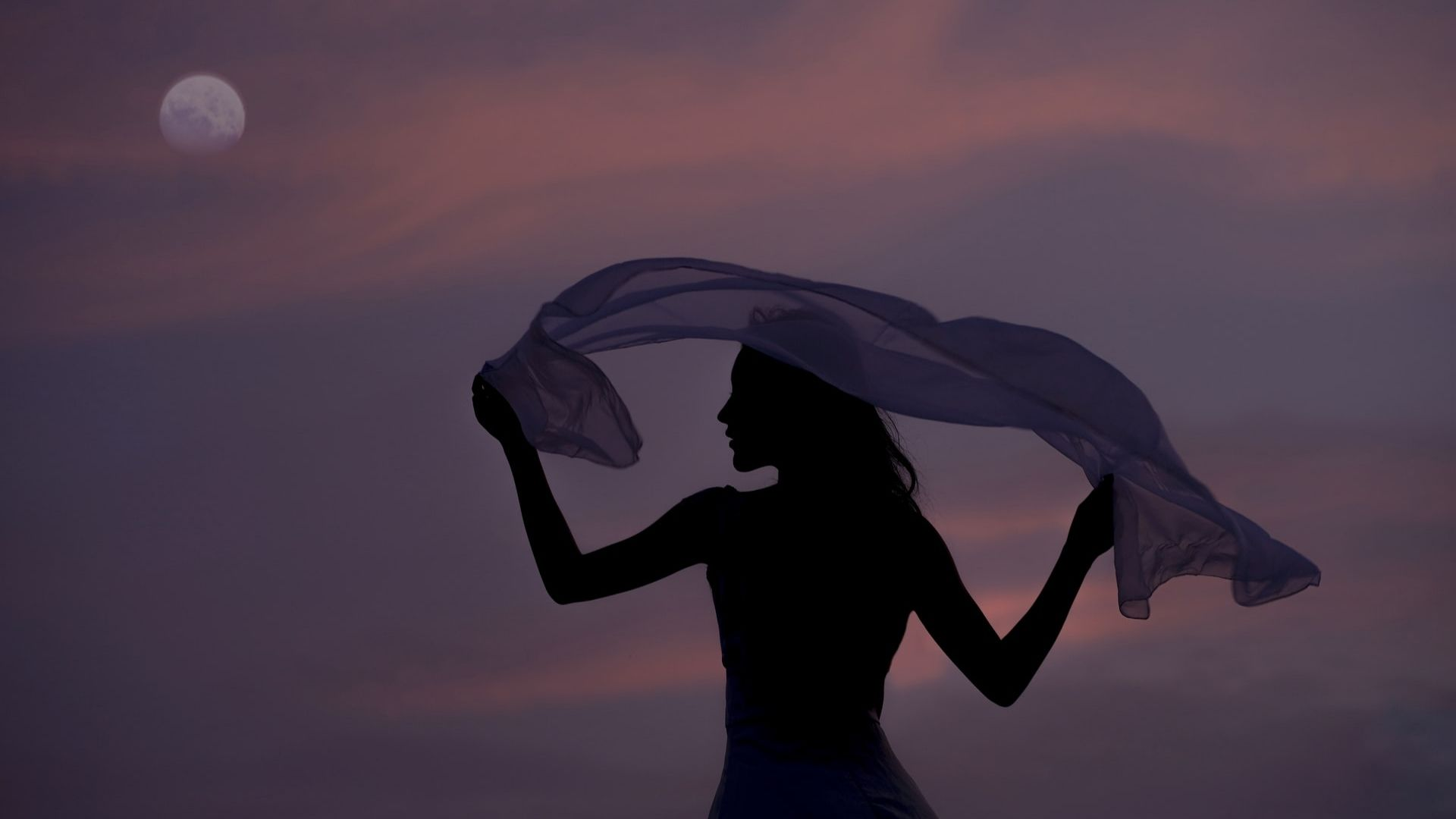 a woman holding a shawl with the sunset and the moon as a backdrop