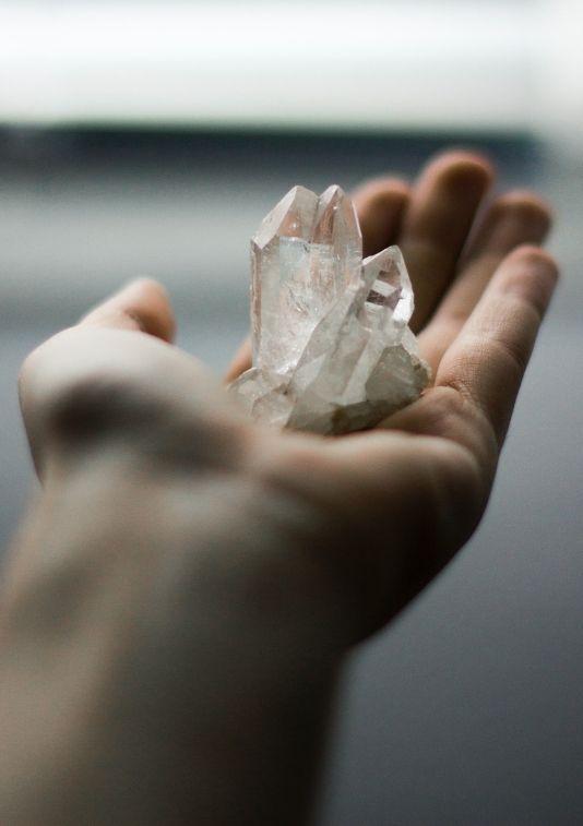 A photo of a hand holding rock quartz