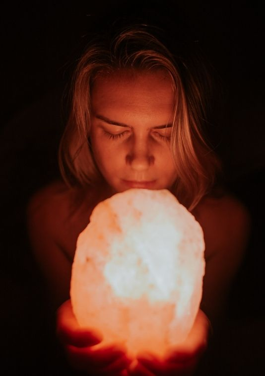 a women holding a lit up crystal in a dark room