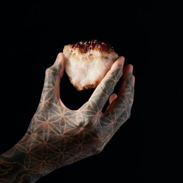 This is a photo of a crystal held in a sacred geometry tattooed hand