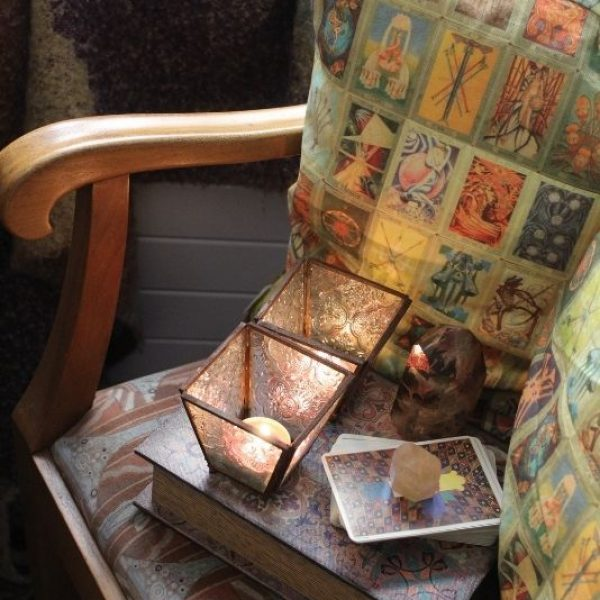 tarot cards, candles and a book on chair